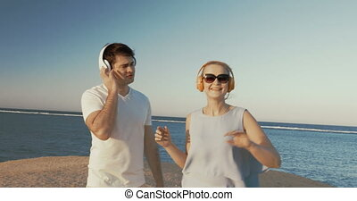 Young people in headphones relaxing on beach - Steadicam...