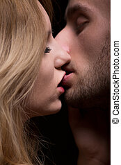 Biting during kiss - Man biting his girlfriend's lip during...