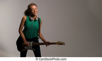 lovely woman plays on guitar and listens to music - young...