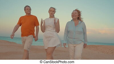Young woman and parents walking on beach - Parents and adult...
