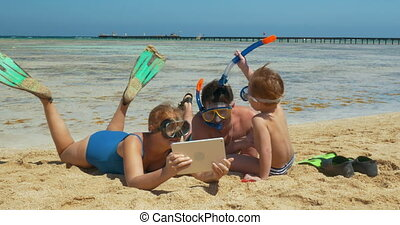 Family Resting on the Beach - Parents and their son are...
