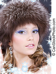 fur - portrait of lovely woman in furry hat over grey