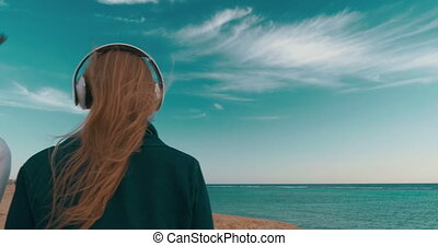 People in Headphones Listening to Music - Steadicam shot of...