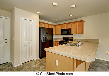 Small kicthen with pantry and black fridge. - Small kitchen...