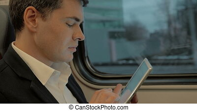 Young businessman chatting on pad in the train