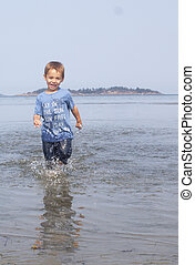 small child running at the beach.