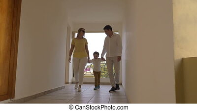 Parents and child in hotel corridor