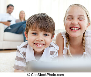 Cute siblings lying on the floor with their parents in the background