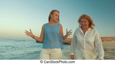 Mother and Daughter Walking by the Sea - Steadicam shot of...