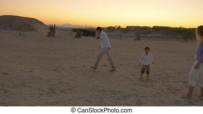 Family Playing Football on a Beach - Steadicam shot of young...