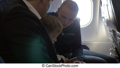 Child and young parents traveling by plane - Family of three...