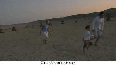 Parents and son playing football on the beach - Steadicam...