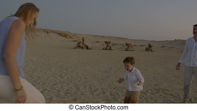 Active game with child on the beach at sunset - Steadicam...