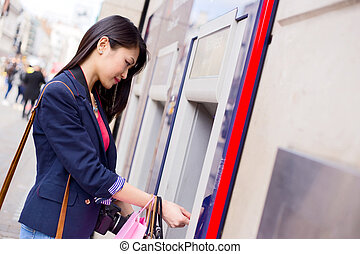 cash machine - young chinese woman withdrawing money at the...