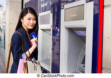 cash machine - young chinese girl at the cashpoint