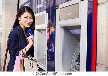 cash machine - young chinese girl at the cash machine