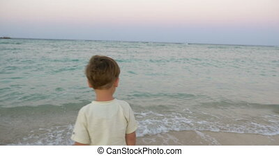 Little child standing by the sea and looking at it