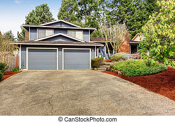 Beautiful blue home with large yard containing grass and soil.