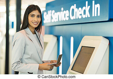 indian businesswoman using self help check in machine