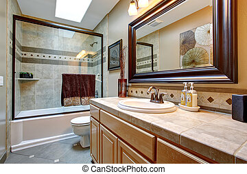 Elegant bathroom with glass shower and large framed mirror.