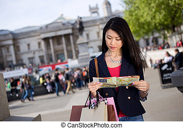 chinese girl reading map - young chinese tourist reading a...
