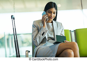 female business traveller talking on cell phone - pretty...