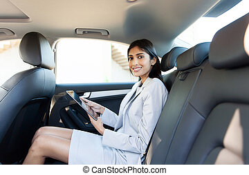 businesswoman with tablet computer in a car