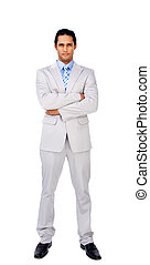 Serious businessman with folded arms against a white...