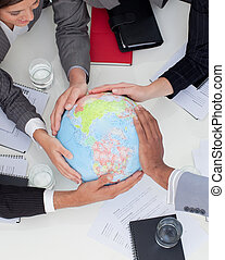 Close-up of multi-ethnic business people holding a terrestrial globe in the office
