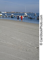 Los Alcazares beach - People walking along a beach promenade...