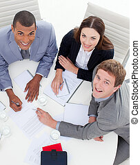 High angle of three multi-ethnic colleagues smiling at the camera in a meeting
