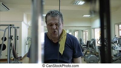 Mature man working out on pulldown machine