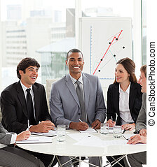 Attractive manager in a meeting with his team smiling at the...