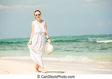 Young woman in long white dress holding hat walks along...