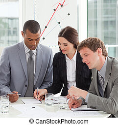 Concentrated business people studying sales report in a...