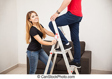 Pretty girl holding a ladder - Beautiful young woman holding...