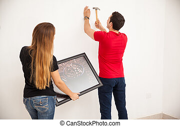 Man helping around the house - Young man nailing a picture...