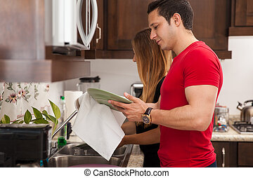 Couple doing the dishes - Profile view of a young couple...