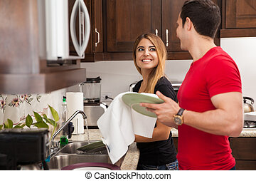 Doing the dishes together - Happy newlyweds washing the...