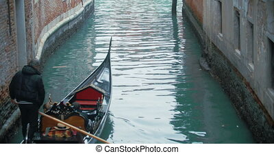 Veteran Gondolier Rowing Gondola along Water Canal in...