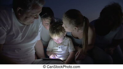 Big Family Watching Bedtime Story on Tablet PC - Little boy...