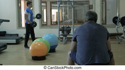 Man exercising with weight disks, his friend having a rest -...