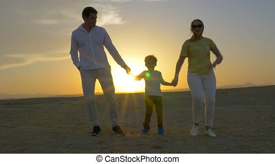 Young Family Dancing on a Beach