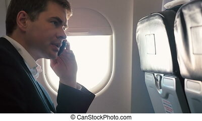 Young man having a business phone talk in plane