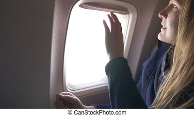 Woman closing blind in plane and using tablet PC - Slow...