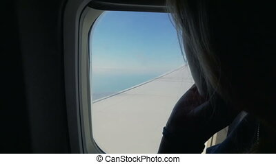 Woman looking out the window in airplane