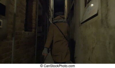 Woman running in narrow street at night - Slow motiona...