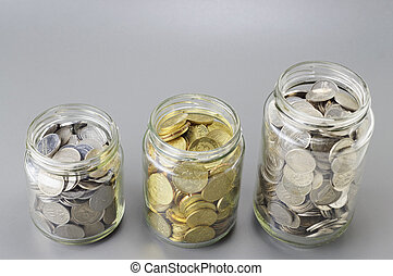 Coins in The Three Different Size of Jar - Financial Concept...