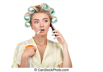Pretty young woman is talking on telephone and smoking -...