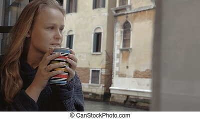 Woman enjoying hot tea and outside view - Slow motion of a...
